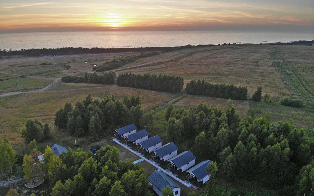 Domki blisko morza na tle zachodu słońca